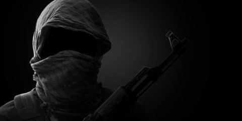 Blurry Background of Terrorist carry weapon hidden in darkness