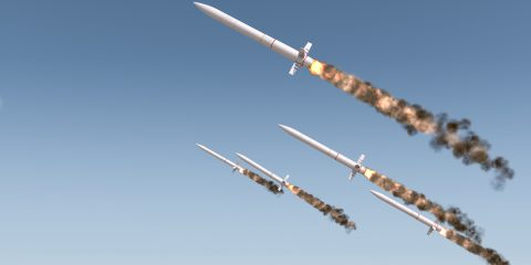 A row of intercontinental ballistic missiles launching in a desert on a blue sky backgrund