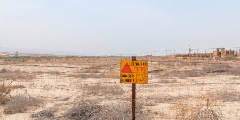 Minefield sign in Hebrew, Arabic, English in Jordan valley, Israel