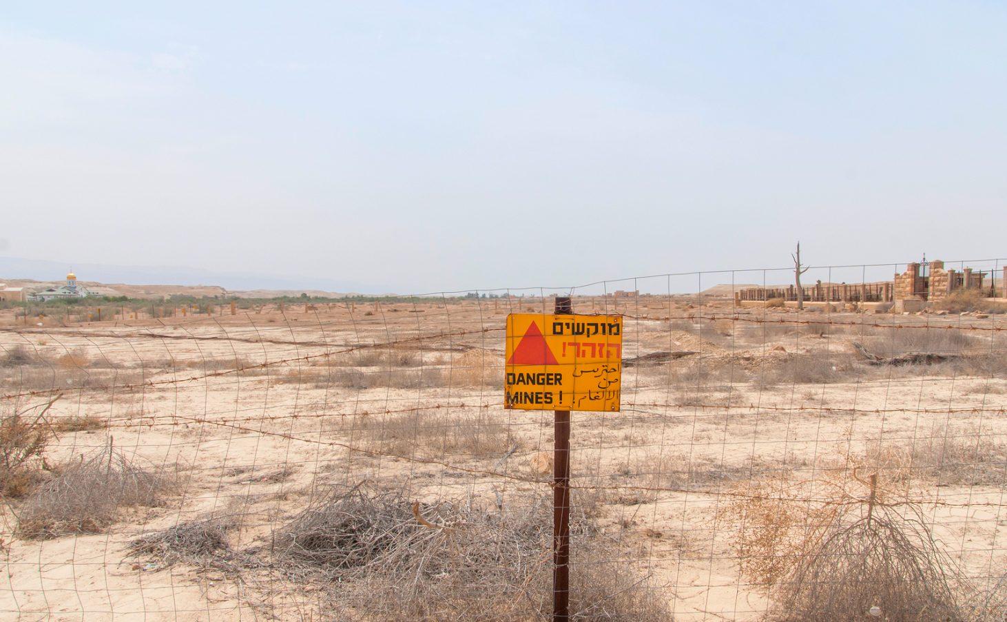 Minefield sign in Hebrew, Arabic, English in Jordan valley, Israel