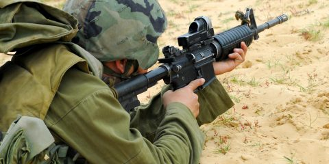 An Israeli defense forces soldier dressed in uniform aims his M16 rifle while on duty