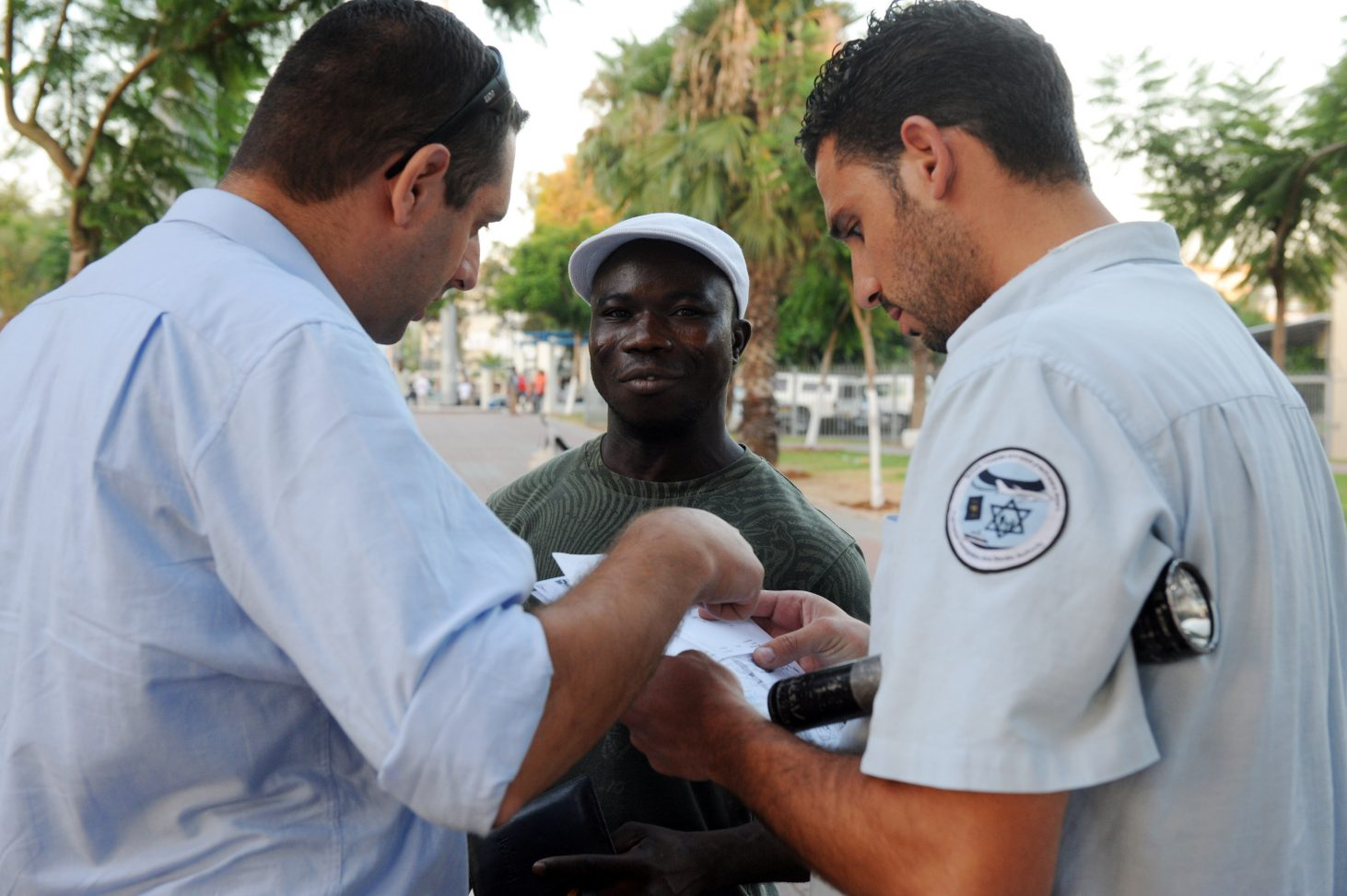 An African talking with police officers in Tel Aviv.