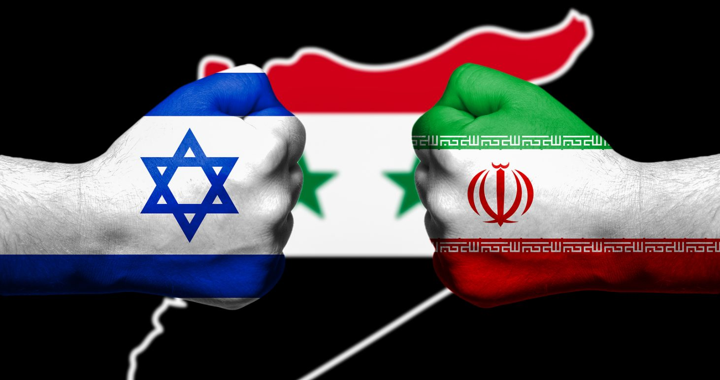 Flags of Israel and Iran painted on two clenched fists facing each other with flag of Syria in the background/Israel - Iran conflict concept