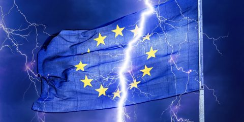 A flash of lightning seems to split an European flag into two parts.