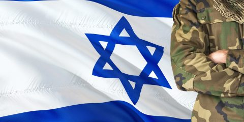 Crossed arms Israeli soldier with national waving flag on background - Israel Military theme.