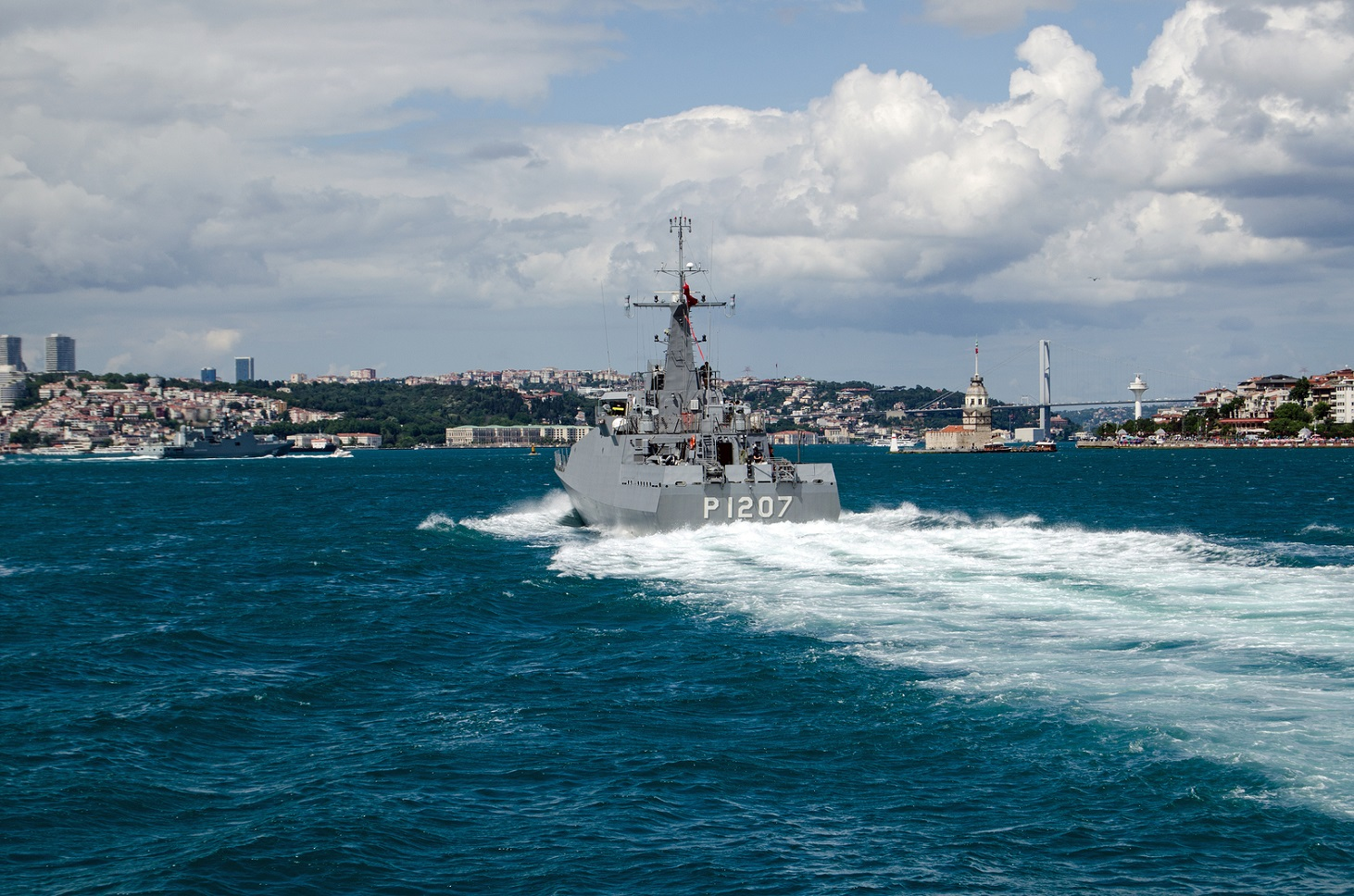 ISTANBUL TURKEY - JUNE 8 2016: The Navy patrol ship Tekirda sailing along the Bosphorus and the landmark Maiden's Tower in Uskudar. The Turkish ship is escorting the larger Russian frigate Admiral Grigorovich which can be seen to the left