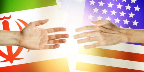 Two hands stretch towards each other against the background. Hands people against the backdrop flags USA and Iran