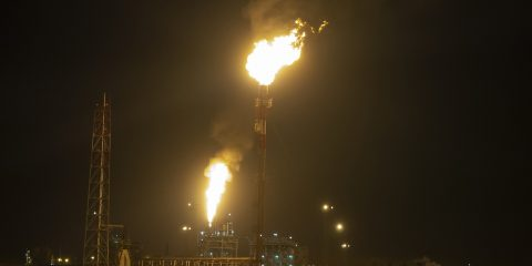 Oil Refinery At Night Creating A Huge Smoke Cloud With Reflectio