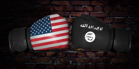 A boxing match. Confrontation between the USA and ISIS. Islamic state and American national flags on Boxing gloves. Sports competition between the two countries. foreign policy conflict.