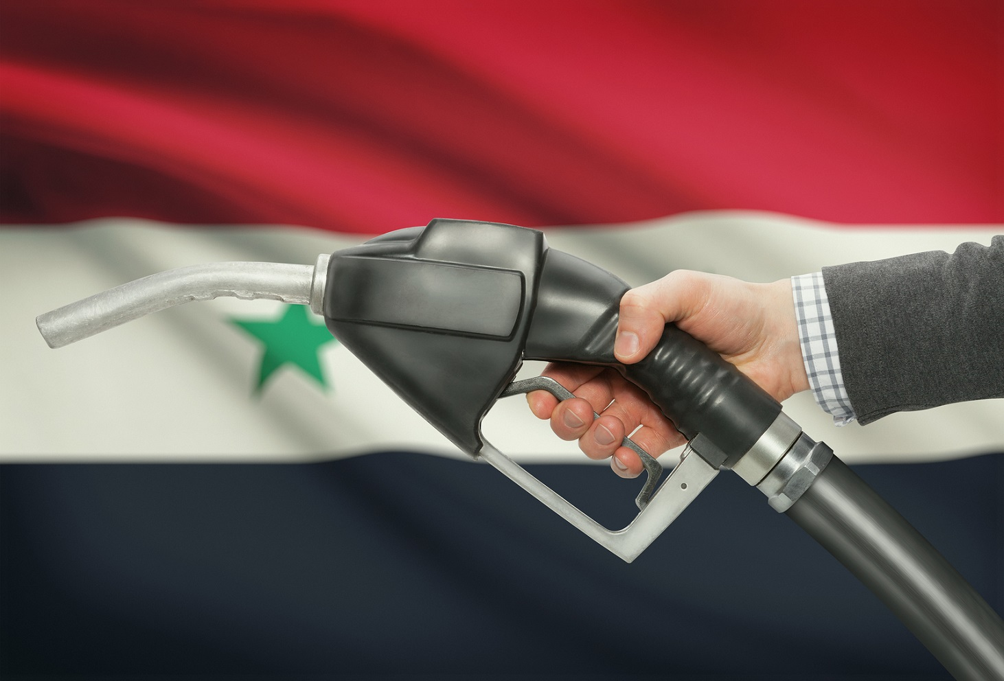 Fuel pump nozzle in hand with flag on background - Syria