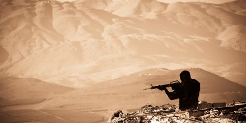 A figure of a Shooting Man with mountains as abackdrop