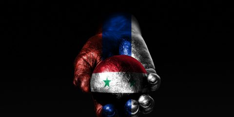 A hand with a drawn Russia flag holds a ball with a drawn Syria flag, a sign of influence, pressure or conservation and protection. Horizontal frame