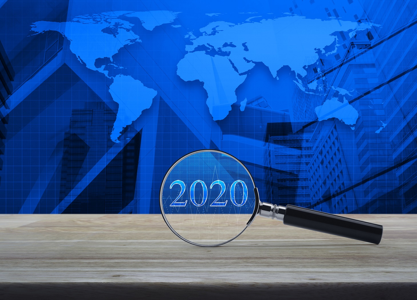 Magnifying Glass With 2020 Text And Financial Graph On Wooden Ta