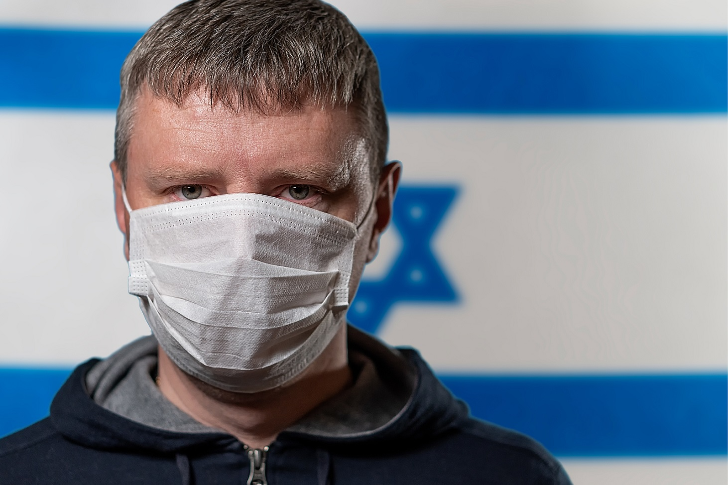 Portrait Of A White Man In A Medical Mask On The Background Of T