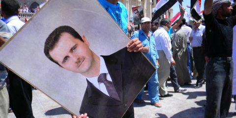 Protestor holding a photo of Assad