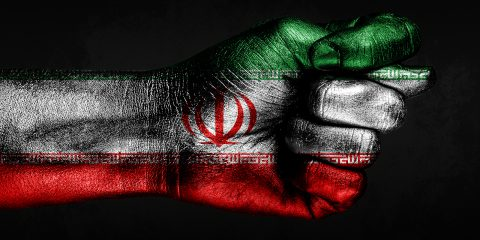 A hand with a painted Iran flag shows a fig, a sign of aggression, disagreement, a dispute on a dark background. Horizontal frame