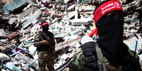 Palestinian militants stand in front of a crashed building
