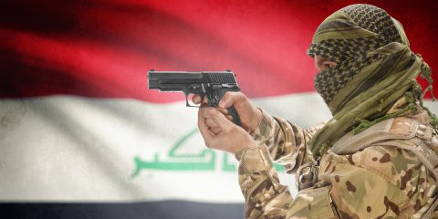 Male with gun in hand and national flag on background series - Iraq