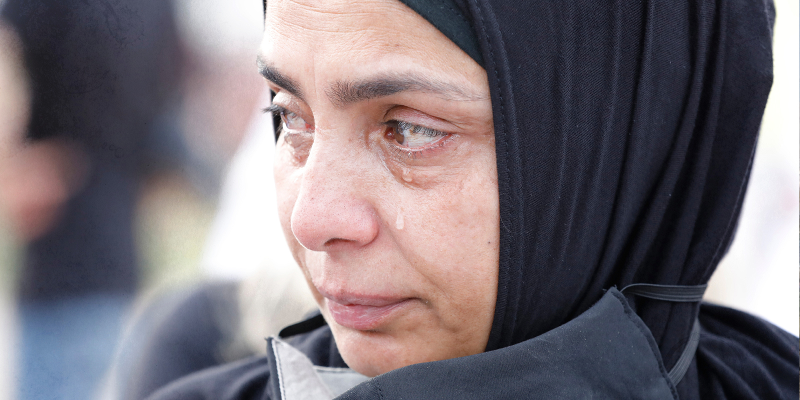 A women in beirut wearing a mask and crying